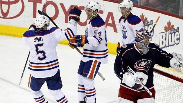 Hokejisté Edmontonu Ladislav Šmíd a Jordan Eberle se radují z gólu do sítě brankáře Columbusu Stevea Masona.