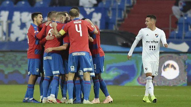 Plzeňští fotbalisté se radují z gólu. Vpravo je smutný Daniel Holzer z Baníku.