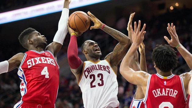 LeBron James z Clevelandu Cavaliers (uprostřed) se snaží prosadit v zápase s Philadelphií.