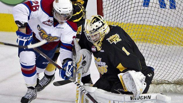 Lotyšský talent Kristians Pelss atakuje brankáře Corbina Boese v utkání zámořské WHL.