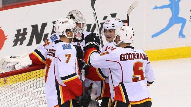 Brankář Calgary Karri Rämö (druhý zleva) slaví se spoluhráči výhru na ledě New Jersey. Raduje se i český útočník Jiří Hudler (druhý zprava).