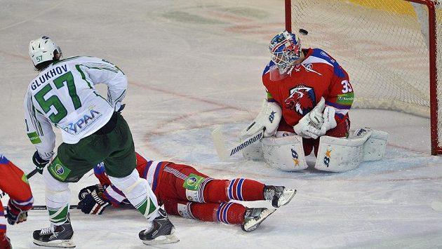Alexej Gluchov z Ufy (vlevo) střílí gól brankáři Lva Praha Petrimu Vehanenovi (vpravo), uprostřed leží na ledě obránce Lva Ondřej Němec.