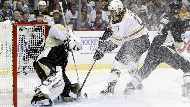 Brankář Pittsburghu Penguins Marc-Andre Fleury (vlevo)kryje střelu útočníka Bostonu Milana Lucice (17).