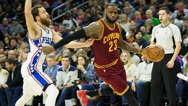 LeBron James z Clevelandu prochází s míčem kolem bránícího Sergia Rodrígueze z Philadelphie.
