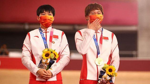 Vítězky týmového sprintu Čung Tchien-š' (vpravo) a Pao Šan-ťü měly na stupních připnuté odznáčky s podobiznou někdejšího komunistického vůdce Mao Ce-tunga.