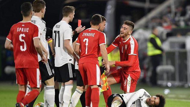 Rozhodčí Bobby Madden ukazuje červenou kartu Milanu Pavkovi (vpravo)ze Srbska za faul na německého reprezentanta Saného.