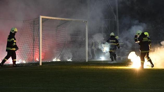 Hasiči sbírají z hřiště světlice, které tam v úvodu utkání naházeli fanoušci Sparty.