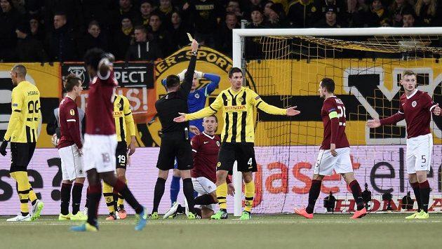 Sparťanský bek Pavel Kadeřábek (na trávníku uprostřed) vidí žlutou kartu za penaltový faul na srbského obránce Bernu Milana Vilotiče (4).