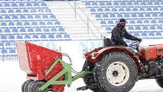 Úklid sněhu z fotbalového hřiště - ilustrační foto.