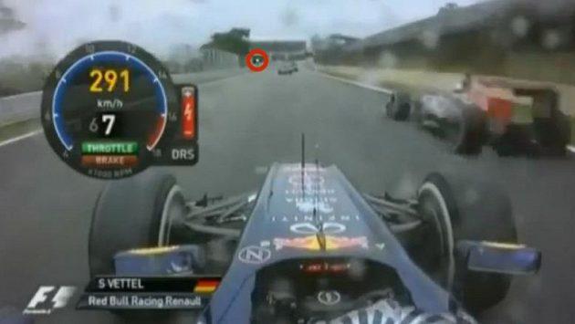 """Fotografie z videa, kvůli kterému Ferrari žádalo po FIA vysvětlení. Sebastian Vettel předjíždí Jeana-Érika Vergneho, přestože je zelená """"vlajka"""" daleko před oběma jezdci."""