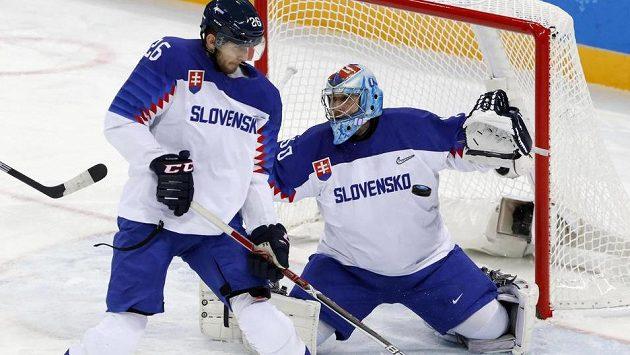 Slovenský brankář Ján Laco řeší za pomoci kolegy z obrany Juraje Mikuše akci amerického týmu v osmifinále olympijského turnaje.