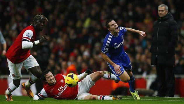 Český fotbalista Arsenalu Tomáš Rosický (ve skluzu) atakuje Cesara Azpilicuetu z Chelsea. Zcela vpravo je trenér Blues José Mourinho.