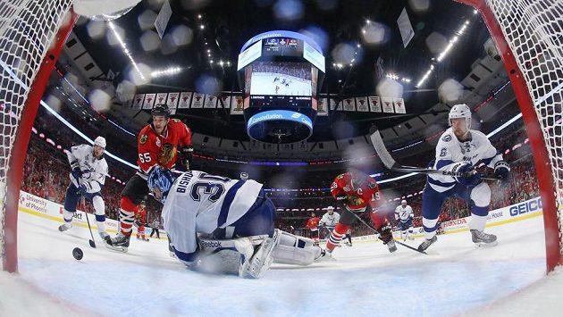 Finále play off NHL, brankář Tampy Bay Ben Bishop (30) zasahuje před útočníkem Chicaga Andrew Shawem (65).