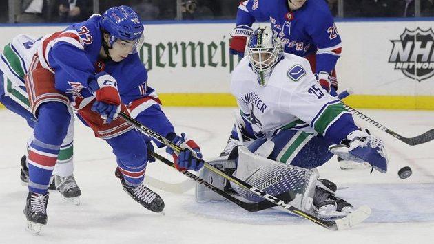 Filip Chytil (72) z NY Rangers se snaží prosadit proti vancouverskému brankáři Jacobu Markströmovi (25).