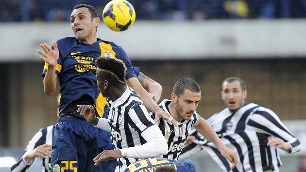 Paul Pogba (uprostřed zády) z Juventusu v souboji s Rafaelem Marquesem z Hellasu Verona.