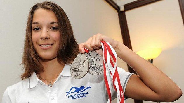 Plavkyně Lucie Svěcená ukazuje dvě medaile z juniorského ME v plavání.