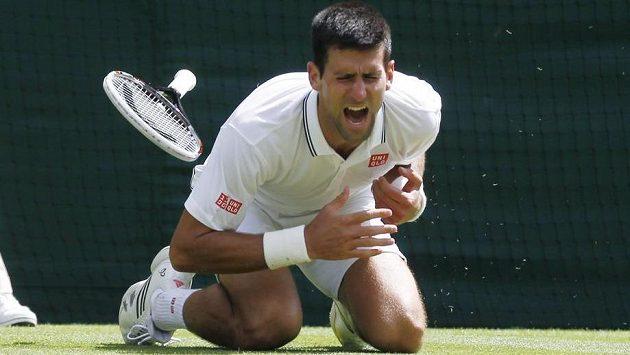 Bolestivá grimasa ve tváři Novaka Djokoviče po pádu na wimbledonské trávě.