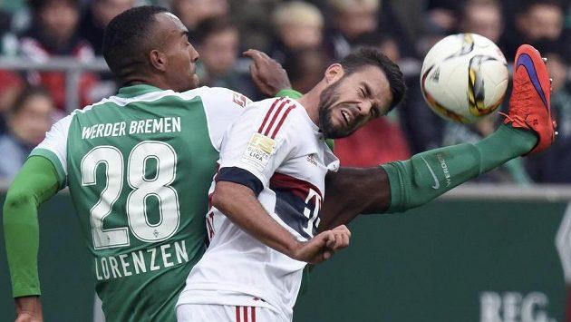 Juan Bernat (vpravo) z Bayernu v tvrdém souboji s Melvynem Lorenzenem z Brém.