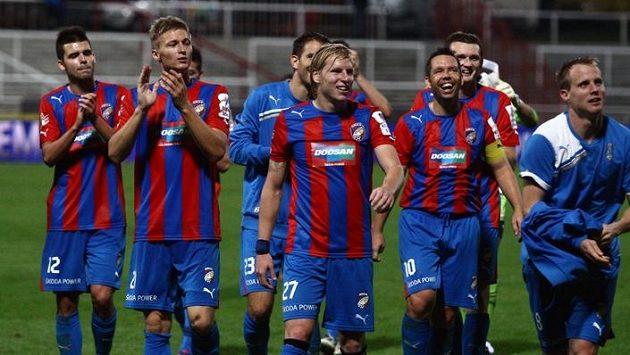 Rozesmátí fotbalisté Plzně oslavují před fanoušky vítězství.