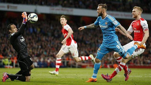Brankář Arsenalu David Ospina takto zlikvidoval šanci Stevena Fletchera ze Sunderlandu.