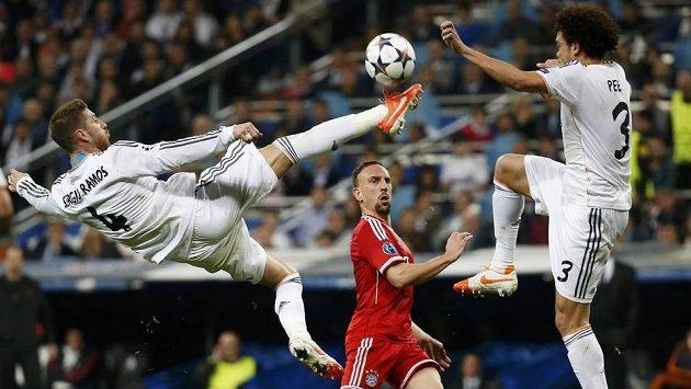Sergio Ramos z Realu při akrobatickém zákroku před Franckem Ribérym z Bayernu v prvním utkání na Santiago Bernabéu.