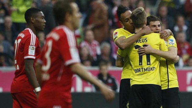 Fotbalisté Dortmundu Pierre-Emerick Aubameyang (třetí zleva), Marco Reus (druhý zprava) a Jonas Hofmann slaví tříbrankové vítězství v mnichovské Allianz areně.