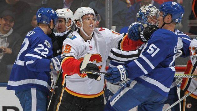 Matthew Tkachuk (uprostřed) z Calgary v souboji s Jakem Gardinerem z Toronta.