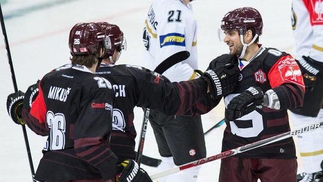 Hokejisté Sparty (zleva) Juraj Mikuš, Jiří Černoch a Brian Ihnacak oslavují gól proti Oulu v prvním utkání.