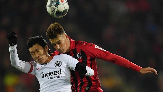 V hlavičkovém souboji o míč se sešli Daiči Kamada (vlevo) z Eintrachtu Frankfurt a Robin Koch z Freiburgu.