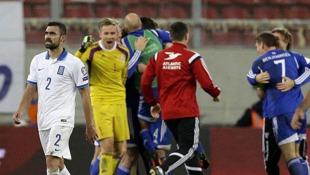 Řek Giannis Maniatis opouští hřiště, na kterém právě hráči Faerských ostrovů oslavují historické vítězství.