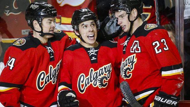 Johnny GÚtočník Calgary Jiřím Hudlerem (vlevo) slaví se spoluhráči Johnnym Gaudreauem (uprostřed) a Seanem Monahanem gól.