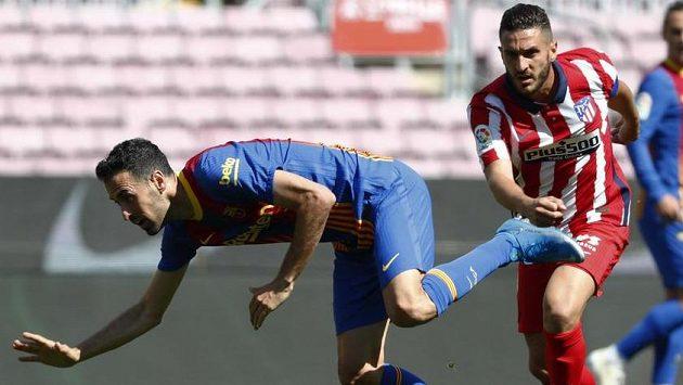 Fotbalista Barcelony Sergio Busquets (vlevo) bojuje o míč s hráčem Atlétika Madrid Koke.