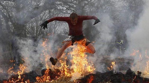 Jeden z účastníků Tough race proskakuje ohnivou hradbou.