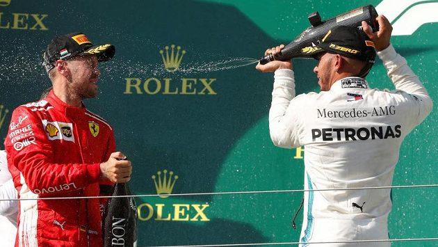 Lewis Hamilton (vpravo) kropí na stupních vítězů Sebastiana Vettela.