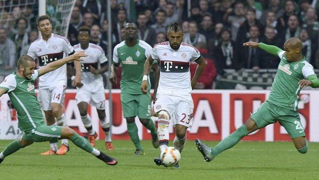 Brémští Theodor Gebre Selassie (vpravo) a Alejandro Galvez se snaží zastavit Artura Vidala z Bayernu.