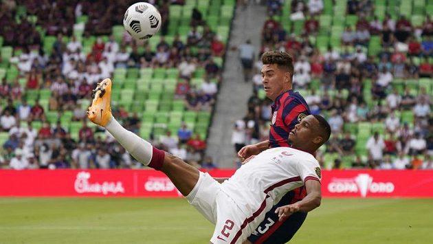 Obránce Kataru Pedro Miguel v souboji o míč s útočníkem USA Matthewem Hoppem.