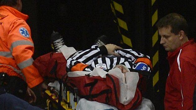 Zraněný hlavní rozhodčí Tomáš Horák opouští po zásahu pukem ledovou plochu na nosítkách.