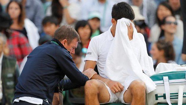 Srb Novak Djokovič v péči fyzioterapeuta při čtvrtfinále s Tomášek Berdychem.