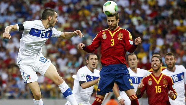 Španělský zadák Gerard Piqué hlavičkuje míč před Leonardem Bonuccim (vlevo) z Itálie v semifinále Poháru FIFA.