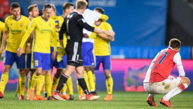 Zklamaný Milan Škoda ze Slavie sleduje radost hráčů Zlína.
