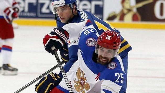 Ruský útočník Danis Zaripov v souboji se švédským forvardem Joakimem Lindströmem.