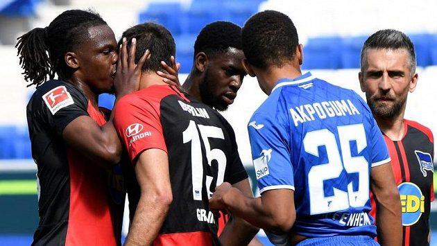 Dedryck Boyata z Herthy se neudržel a políbil Marka Grujiče, druhý zprava je hoffenheimský Kevin Akpoguma, který vlastním gólem hosty poslal do vedení.