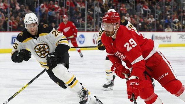 Levé křídlo Detroitu Brendan Perlini veze kotouč před obráncem Bostonu Bruins Brandonem Carlem.