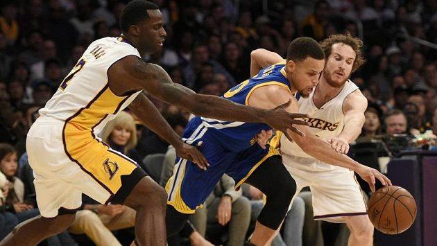 Stephen Curry z Golden State se probíjí přes dvojici bránících soupeřů z Los Angeles Lakers Brandona Basse (vlevo) a Marcela Huertase.