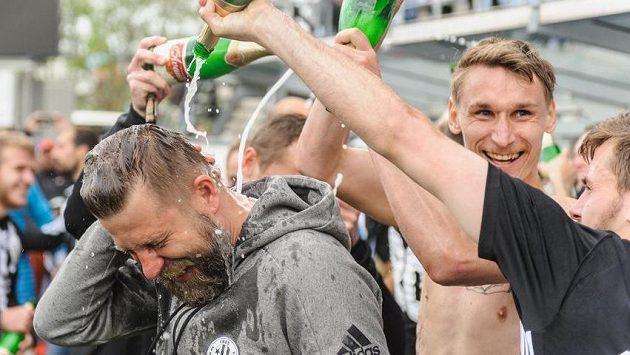 Hráči Českých Budějovic se radují z postupu a trenér David Horejš (v popředí) dostává svou dávku šumivého vína.
