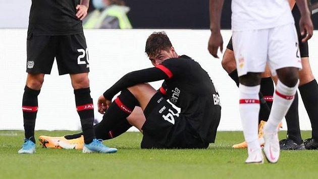 Zraněný fotbalista Leverkusenu Patrik Schick sedí na trávníku během utkání s VfB Stuttgart.