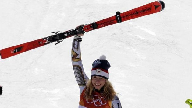 Ester Ledecká na zlatém stupínku pózuje i s lyžemi od Mikaely Shiffrinové.