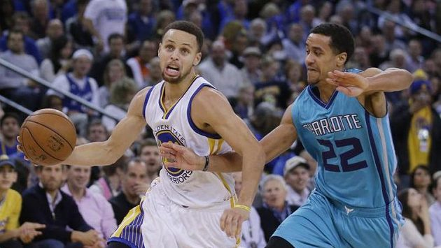 Stephen Curry (vlevo) z Golden State a Brian Roberts (22) z Charlotte.