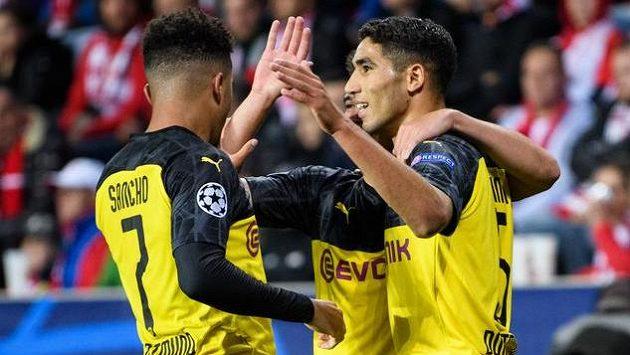Fotbalisté Dortmundu Jadon Sancho (vlevo), Raphael Guerreiro a Achraf Hakimí oslavují během utkání základní skupiny Ligy mistrů na hřišti Slavie Praha.