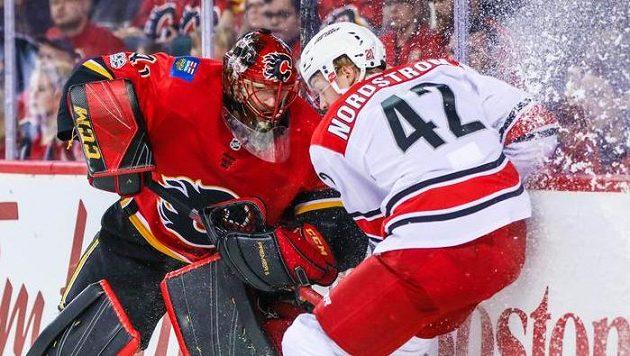 Brankář Calgary Mike Smith se snaží rozehrát puk před křídelníkem Joakimem Nordströmem z Caroliny.